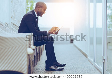 Checking his business schedule. Side view of cheerful young African businessman working on digital tablet while sitting on the chair - stock photo
