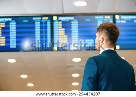 Checking his flight data. Rear view of handsome businessman in formalwear checking time and looking at flights schedule while standing in the airport - stock photo