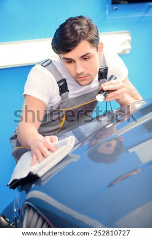 Checking his ideal work. Portrait of a handsome car mechanic polishing the luxury car with wiper and lighter in car repair shop - stock photo