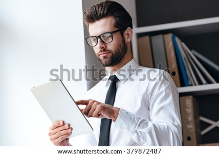 Checking his mail. Pensive young handsome businessman in glasses using his touchpad while standing in office  - stock photo