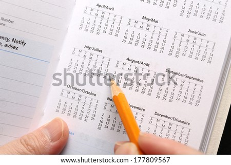 Checking important date on calendar - stock photo