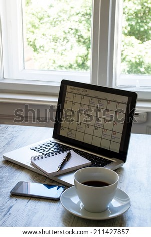 Checking monthly activities and appointments at the office in the laptop  - stock photo
