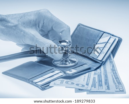 Checking open wallet with stethoscope. Concept of financial crisis or healthcare costs - stock photo
