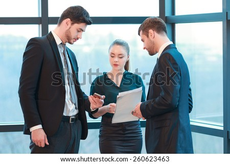 Checking schedule with colleagues. Group of business people in formal wear looking at the screen of mobile phone while standing against the window in the meeting room - stock photo