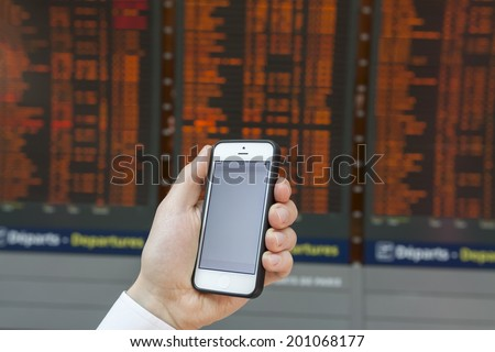Checking smartphone screen at flight information board timetable in airport - stock photo