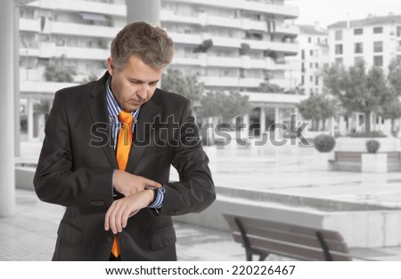 Checking the time. Worried adult businessman - stock photo