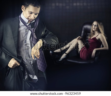 Checking the time. Worried young business man is late. Or man run away from his mistress, quickly dressed to get somewhere in time - stock photo