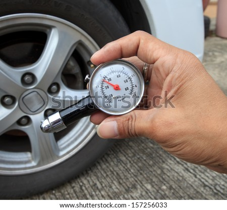checking tire air pressure with meter  gauge before traveling for multipurpose - stock photo