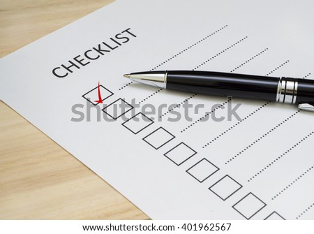 Checklist concept - checklist box with red checkmark, paper and a pen with checklist word on wooden table - stock photo