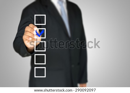 checklist on whiteboard with businessman hand drawing a blue check mark in one checkbox - stock photo