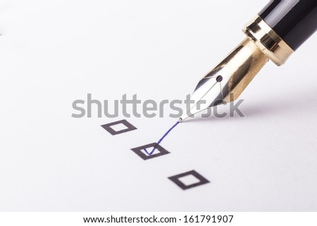 Checklist with the second option checked and a fountain pen on white page - stock photo