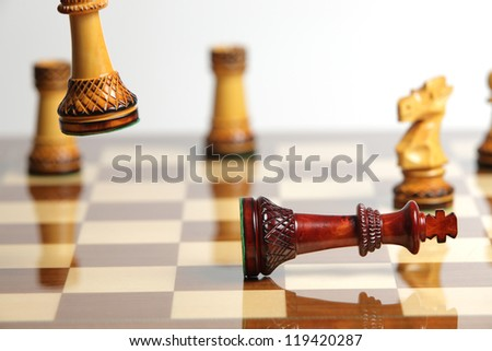 Checkmate with wooden chess pieces on a reflective chessboard - stock photo