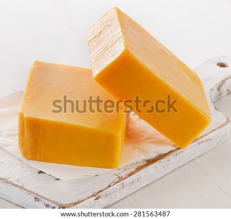 Cheddar Cheese on a white Cutting Board. Selective focus - stock photo