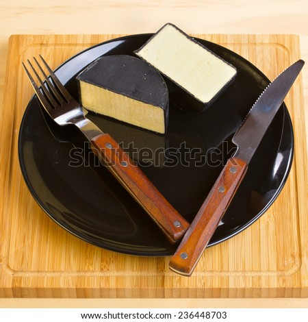 Cheddar cheese on black plate with fork and knife. Wooden board as a background - stock photo