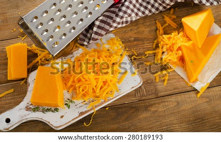 Cheddar Cheese on white cutting Board. Top view - stock photo