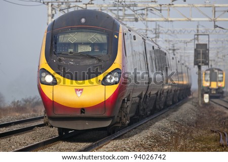 CHEDDINGTON, ENGLAND - JANUARY 13: A Virgin Pendolino express heads towards London on January 13, 2012 at Cheddington. Virgin topped the performance table for long distance UK rail operators in 2011 - stock photo