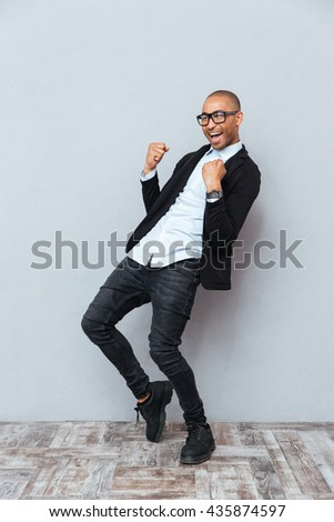 Cheeful african american young man celebrating success - stock photo
