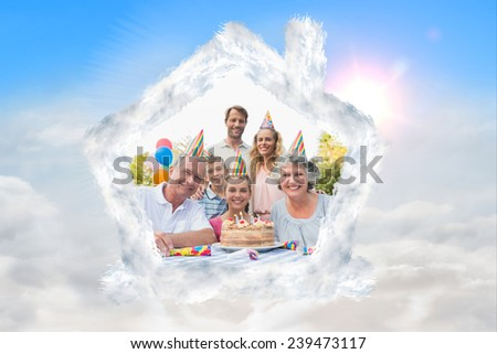Cheeful family smiling at camera at birthday party against blue sky with white clouds - stock photo