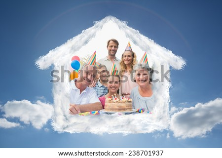Cheeful family smiling at camera at birthday party against cloudy sky with sunshine - stock photo