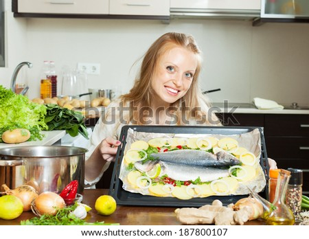 Cheeful housewife cooking fish and potatoes in sheet pan at home - stock photo