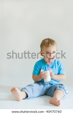 cheeky cute boy with glass of milk - stock photo