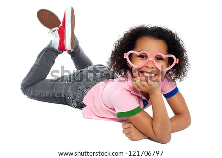 Cheeky expression of a relaxed young girl wearing heart shaped eyeglasses. - stock photo