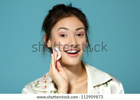 Cheer attractive teen girl clean her face with cotton disk. Morning theme. Over blue background. - stock photo