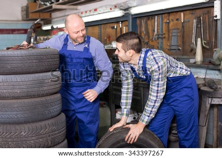 Cheerful adult mounting specialists working at auto repair shop. Focus on the right man - stock photo