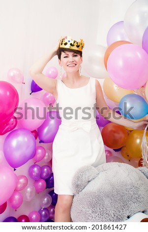 Cheerful adult woman tries on toy crown - stock photo