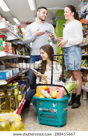 Cheerful adults people standing near shelves with canned goods at shop - stock photo