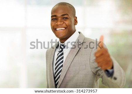 cheerful african american business executive giving thumb up in office - stock photo