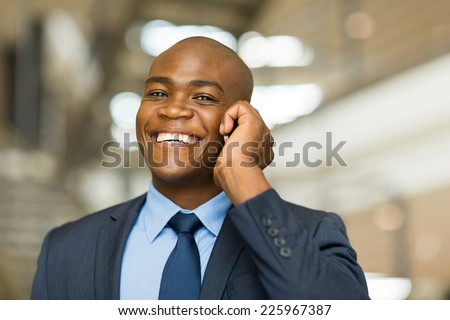 happy cheerful young black businessman walking and talking