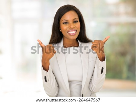 cheerful african american businesswoman giving thumbs up - stock photo