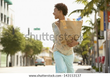 Cheerful African American woman carrying grocery bag while walking on street - stock photo