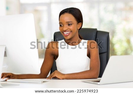 cheerful african businesswoman working on computer - stock photo
