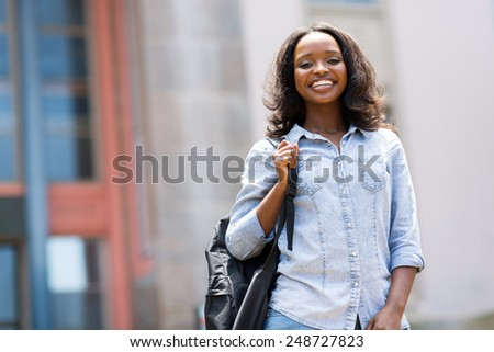cheerful african college girl outdoors on modern campus - stock photo