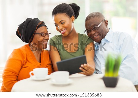 cheerful african family at home using tablet pc - stock photo