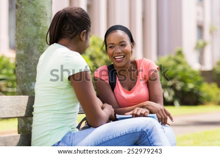 cheerful african female students sitting on bench at university campus - stock photo