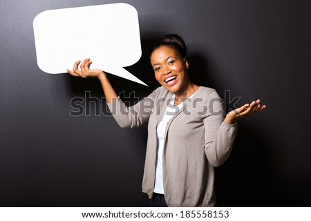 cheerful african girl holding blank speech bubble on black background - stock photo