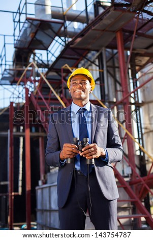 cheerful african industrial manager with binoculars in fuel refinery - stock photo