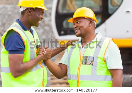 cheerful african mine workers hands together to form brotherhood - stock photo
