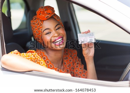 cheerful african woman showing a driving license she just got - stock photo
