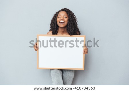 Cheerful afro american woman showing blank board over gray background - stock photo
