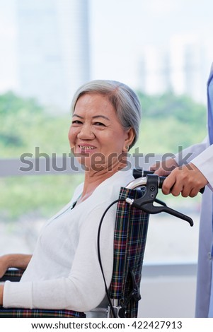 Cheerful aged woman in wheelchair after treatment in hospital - stock photo