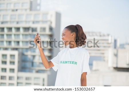 Cheerful altruist woman looking at her mobile phone outdoors on urban background - stock photo