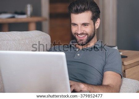 Cheerful and handsome blogger. Cheerful handsome young man using his laptop with smile while sitting on the couch at home - stock photo
