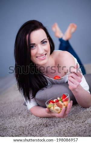 cheerful and healthy young woman brunette eating fruit salad at home - stock photo