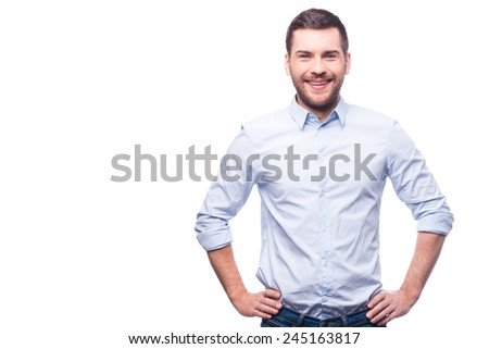 Cheerful and stylish. Handsome young man in shirt looking at camera and holding hands on hips while standing against white background  - stock photo