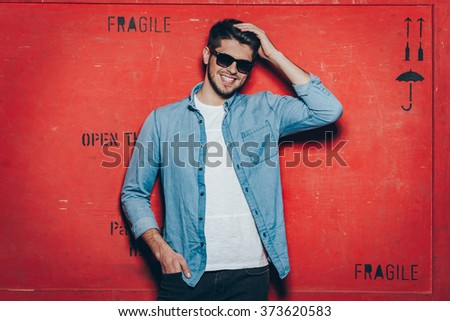 Cheerful and trendy.Handsome young cheerful man in sunglasses keeping hand in hair and looking at camera with smile while standing against red background - stock photo