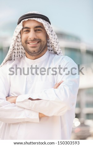 Cheerful Arab businessman. Smiling Arab businessman holding his arms crossed and looking at camera - stock photo